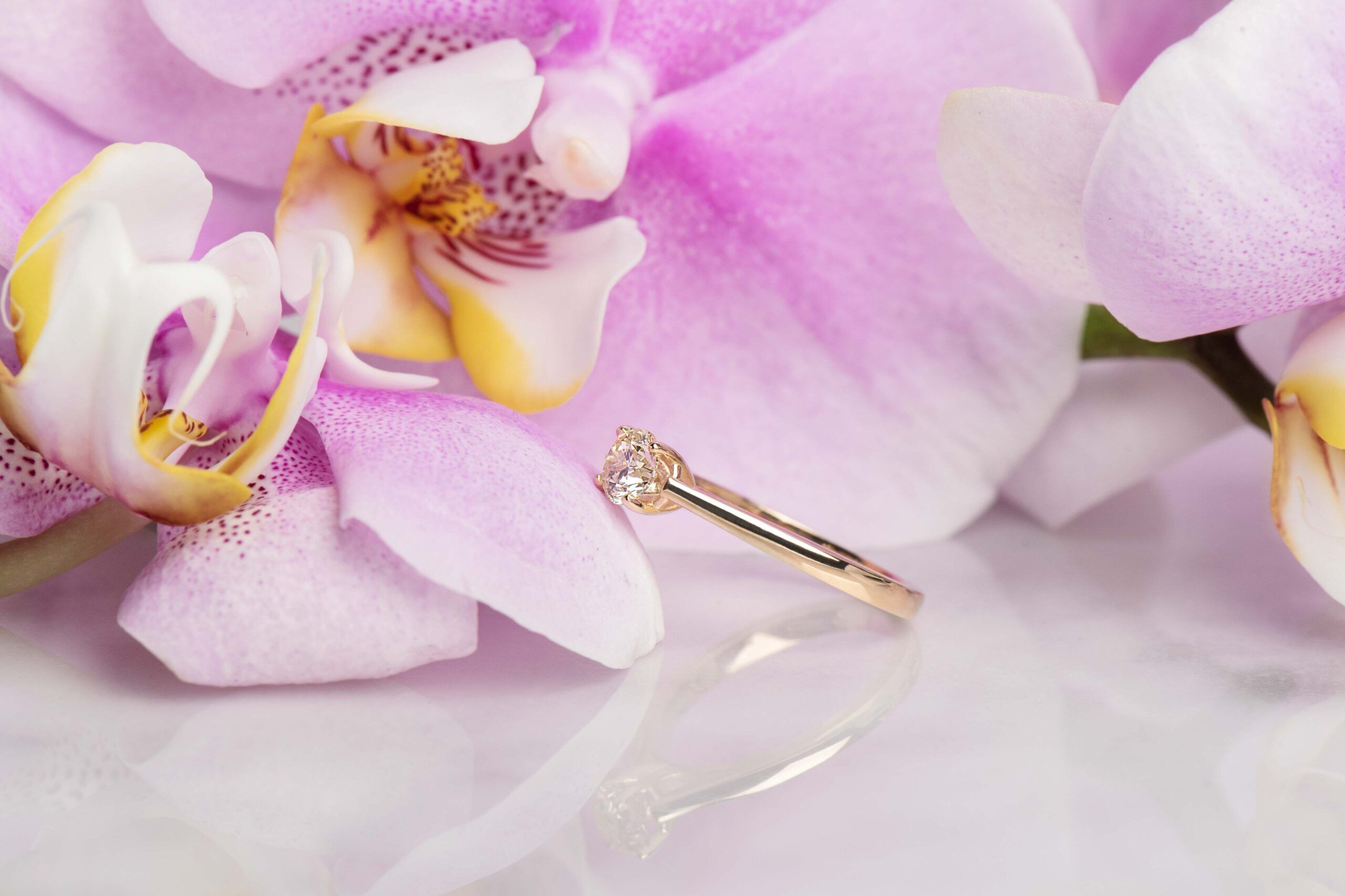 Diamond with gold band on orchids and marble
