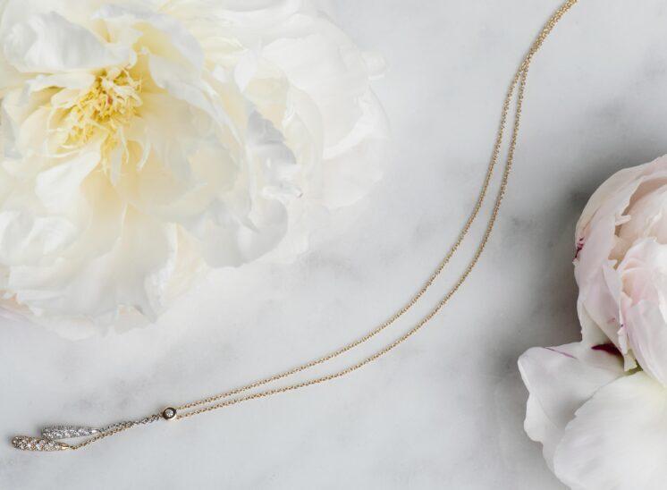 Diamond pendant on marble with peonies
